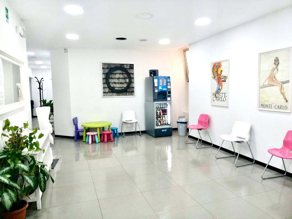 Panoramica della sala d'attesa con angolo ristoro e area bimbi.